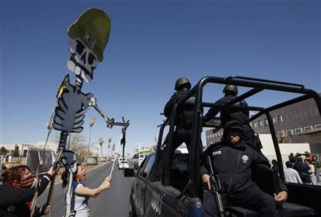 People carry a placard in the shape of a skeleton with a gun made out of carton during a protest outside the U.S. consulate in Ciudad Juarez March 5, 2011. REUTERS/Gael Gonzalez