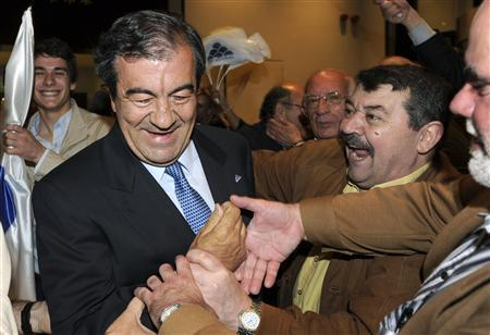 Supporters congratulate Foro Asturias candidate to regional presidency of Asturias, Francisco Alvarez-Cascos (L), after his victory at the regional elections in downtown Oviedo, late May 22, 2011. REUTERS/Eloy Alonso