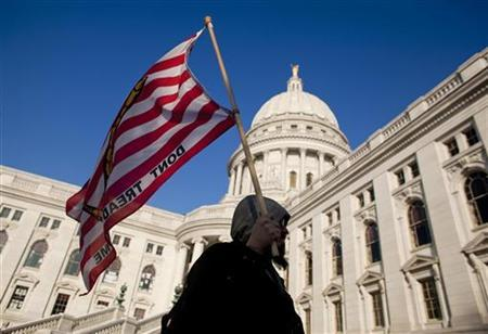 A man marches with a ''don't tread on me'' flag outside the State Capitol building as they wait to occupy it during day fourteen of their protest against the proposed budget cuts by Wisconsin Governor Scott Walker in Madison, Wisconsin February 28, 2011. REUTERS/Darren Hauck