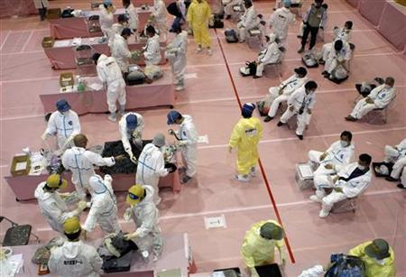 Evacuees from Kawauchi village wearing protective suits undergo a screening test for signs of nuclear radiation after returning from a brief trip back to their homes inside the restricted zone of a 20 km radius around the crippled Fukushima Daiichi Nuclear Power Plant, at a gymnasium in Kawauchi village, about 22 km (14 miles) from the plant in Fukushima prefecture May 10, 2011. REUTERS/Issei Kato