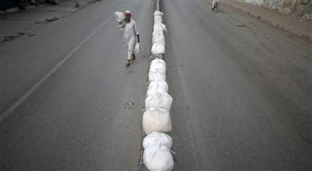 A man carries bags of condensed milk cream as he shifts them from one side of a road to the other side in Abbottabad May 17, 2011, the city where U.S. Navy SEAL commandos killed al Qaeda leader Osama bin Laden May 2, 2011. REUTERS/Akhtar Soomro