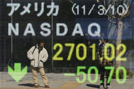 Passersby are reflected in an electric board displaying a downward arrow for the Nasdaq index outside a brokerage in Tokyo March 11, 2011. REUTERS/Toru Hanai