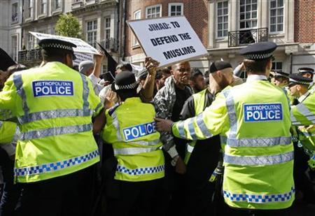 Muslims are restrained by police officers during their protest march towards the U.S. Embassy, after an English Defence League (EDL) demonstrator attempted to attack them, in London May 6, 2011. REUTERS/Suzanne Plunkett