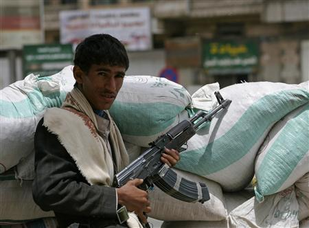 An armed tribesman loyal to the tribal leader Sadiq al-Ahmar stands behind sandbags as he secures a street leading to his house during clashes in Sanaa May 26, 2011. REUTERS/Khaled Abdullah
