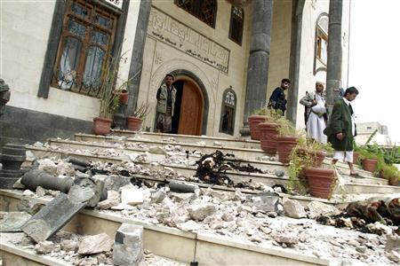 Armed guards stand on stairs littered with wreckage after shelling by police forces on the house of Yemeni tribal leader Sadiq al-Ahmar in Sanaa May 26, 2011. REUTERS/Khaled Abdullah