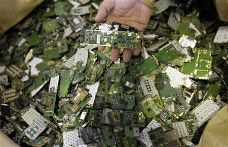 A worker holds parts of a scrap mobile phone, at a recycling facility of Re-Tem Corp, in Tokyo October 15, 2010. REUTERS/Toru Hanai