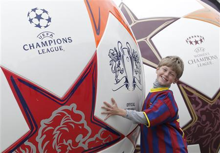 A fan of Barcelona football team poses between two football sculptures promoting the Champions League final against Manchester United in Trafalgar Square in London May 27, 2011. REUTERS/Luke MacGregor