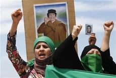 <p>EDITOR'S NOTE: PICTURE TAKEN ON A GUIDED GOVERNMENT TOUR Women shout pro-Gaddafi slogans during the funeral of people killed in air strikes by coalition forces last night, at the martyrs' cemetery in Tripoli May 14, 2011. REUTERS/Louafi Larbi</p>