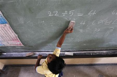 A student cleans a blackboard at a school in suburban Bangkok February 14, 2011. REUTERS/Sukree Sukplang