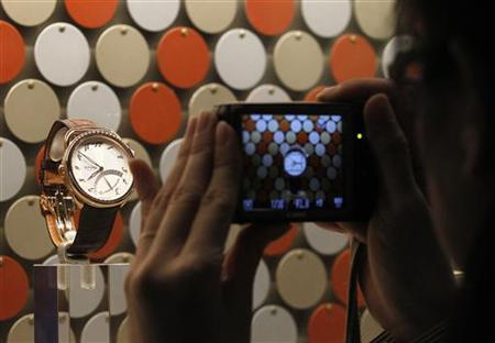 A woman takes pictures of a watch displayed at Hermes showcase at Baselworld fair in Basel March 24, 2011. REUTERS/Christian Hartmann