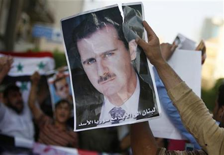 A Syrian living in Lebanon holds a poster of Syria's President Bashar al-Assad during a pro-government protest, while an anti-government protest takes place a few metres away at the same time in Beirut May 23, 2011. REUTERS/ Jamal Saidi