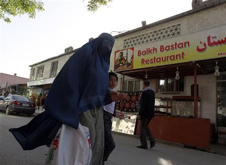 An Afghan woman clad in burqa and her daughter walks past a restaurant built inside part of the only synagogue building in Kabul, June 1, 2011. REUTERS/Omar Sobhani