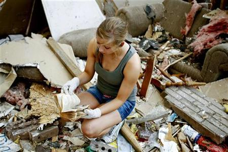 Volunteer Mackenzie Finklea, of Quincy, Il., looks through a cookbook in a house destroyed by the May 22 tornado in Joplin May 31, 2011. REUTERS/Sarah Conard