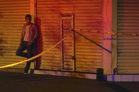 A passer-by looks on near a crime scene where a man had been killed earlier in a shootout in downtown Guadalajara February 7, 2011. REUTERS/Alejandro Acosta