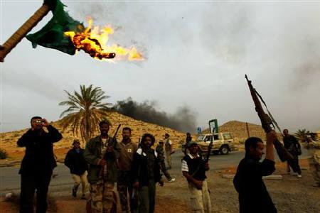 Rebel fighters burn a Libyan national flag after they  took over the Bir Ayyad gate near the city of Zintan in the Western Mountains, some 120 km (75 miles) southwest of the capital Tripoli, June 3, 2011. REUTERS/Youssef Boudlal