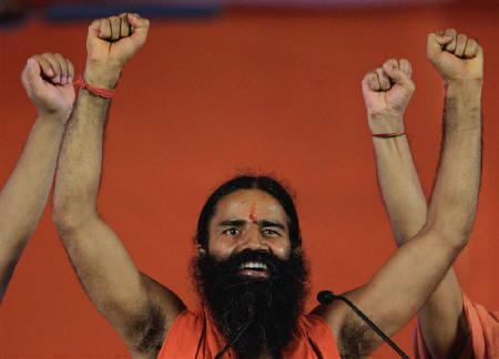 Yoga guru Swami Ramdev raises his hands with supporters at the Ramlila grounds on the first day of his fast in New Delhi June 4, 2011. REUTERS/Adnan Abidi
