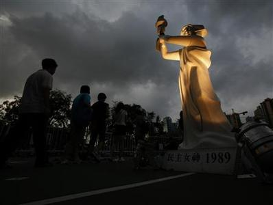 People walk past a replica of the Goddess of Democracy as they enter Hong Kong's Victoria Park to take park in a candlelight vigil June 4, 2011, to mark the 22nd anniversary of the military crackdown of the pro-democracy movement at Beijing's Tiananmen Square in 1989. REUTERS/Bobby Yip