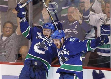 Vancouver Canucks left wing Alex Burrows (L) celebrates his game-winning goal on the Boston Bruins with Daniel Sedin during overtime in Game 2 of the NHL Stanley Cup Final hockey playoff in Vancouver, British Columbia June 4, 2011. REUTERS/Mike Blake