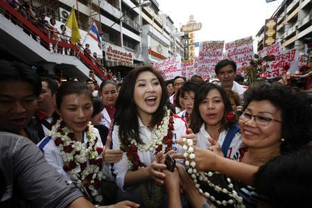 Yingluck Shinawatra (C), toppled premier Thaksin Shinawatra's sister and the prime ministerial candidate for country's biggest opposition Pheu Thai Party, is welcomed by supporters in Chiang Mai May 21, 2011. Ahead of a July 3 national election, dozens of rural communities are branding themselves ''Red Shirt Villages'' in Thailand's poor northeast plateau, a traditional red-shirt bastion and home to a third of Thailand's population, giving the movement grass-roots muscle to mobilise behind its parliamentary allies, the opposition Puea Thai Party. Picture taken May 21, 2011. REUTERS/Dario Pignatelli/Files