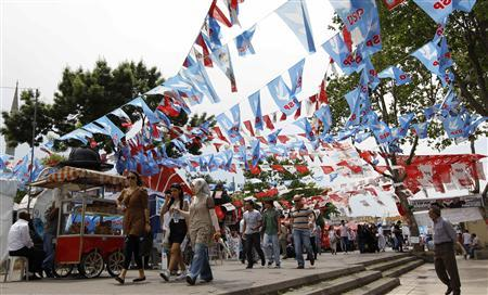 People walk under the flags of political parties in Istanbul June 10, 2011. REUTERS/Murad Sezer