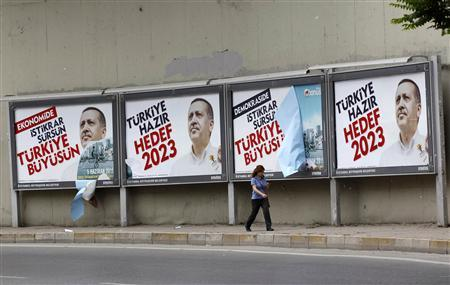 A woman walks past Turkish Prime Minister Tayyip Erdogan's election campaign posters in Istanbul June 10, 2011. Turkey will hold parliamentary elections on June 12. The posters read, ''Stability proceeds, Turkey grows'' and ''Turkey is ready, Target is 2023''. REUTERS/Murad Sezer