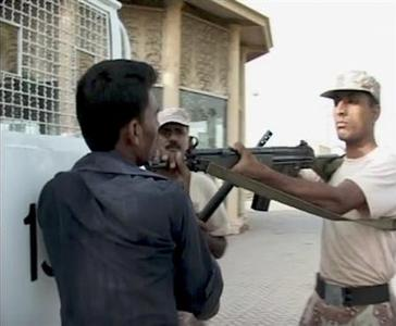 A man identified as Sarfaraz Shah (L) holds the barrel of a weapon of a paramilitary Ranger at a park in the southern city of Karachi shortly before he was shot dead, in this still image taken from video June 8, 2011. REUTERS/Awaz TV via Reuters TV