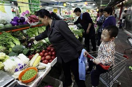 A woman selects vegetables next to a shopping cart carrying her child at a market in Beijing May 11, 2011. REUTERS/Jason Lee