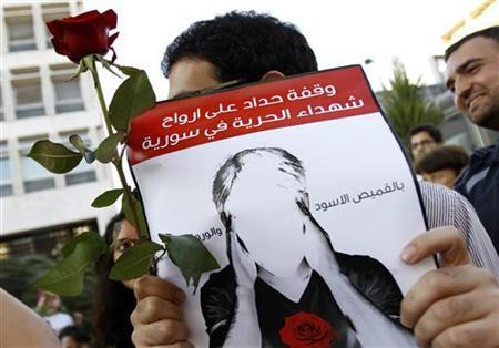 A Lebanese activist holds up a sign and a flower during a demonstration to show solidarity with Syria's anti-government protesters, in Beirut May 23, 2011. The banner reads, ''The vigil for the souls of the martyrs of freedom in Syria.'' REUTERS/ Jamal Saidi