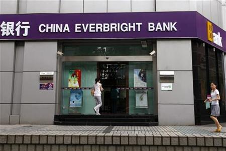 Passers-by walk past a branch of China Everbright Bank in Shanghai in this July 26, 2010 file photo. REUTERS/Aly Song