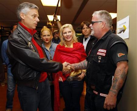 Former U.S. ambassador to China and possible Republican presidential candidate Jon Huntsman (L) greets a motorcycle rider, as Huntsman's wife Mary Kaye (C) and daughter Liddy look on, at a Harley Davidson store in Manchester, New Hampshire June 11, 2011. REUTERS/Brian Snyder