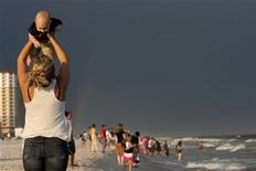<p>A woman lifts her son on Pensacola Beach, REUTERS/Colin Hackley</p>