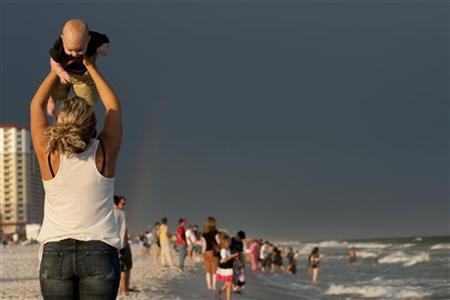 A woman lifts her son on Pensacola Beach, REUTERS/Colin Hackley