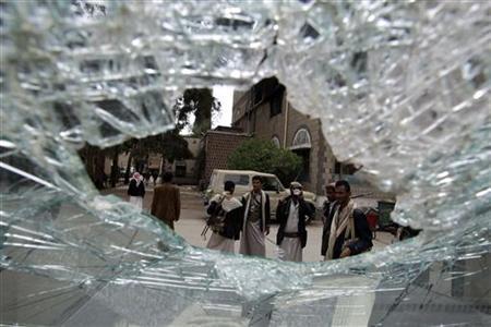 Armed guards, seen through a shattered window, walk near damaged cars at the house of Yemeni tribal leader Sadiq al-Ahmar in Sanaa June 13, 2011.REUTERS/Ammar Awad