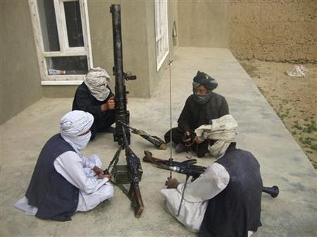Taliban fighters pose with weapons as they sit in their compound at an undisclosed location in southern Afghanistan in this May 5, 2011 picture. REUTERS/Stringer