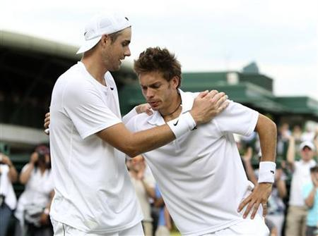 John Isner of the U.S. (L) embraces France's Nicolas Mahut after defeating him at the 2010 Wimbledon tennis championships in London, June 24, 2010. REUTERS/Pool