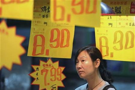 A customer looks at price tags in a supermarket in Hefei, Anhui province May 11, 2011. REUTERS/Stringer