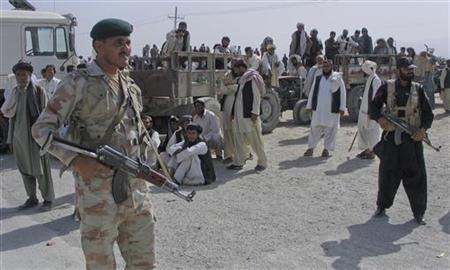 Paramilitary forces stand guard as tribesmen block a road in Chaman along the Afghan border June 17, 2011. About 300 Pakistani tribesmen have blocked NATO supplies and other traffic at an Afghan border crossing to protest an alleged shooting incident involving Afghan border guards and Pakistani and Afghan tribesmen a day earlier, local media reported. REUTERS/Saeed Ali Achakzai
