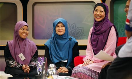 ''Solehah'' hopefuls Amie Sofia Ahmad (L) and Arina Ramlan smile as they are being interviewed on a morning talk show before their audition for the new Islamic reality TV show ''Solehah'' in Kuala Lumpur June 18, 2011. REUTERS/Bazuki Muhammad