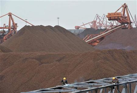 Labourers work at an iron ore storage site at Yingkou Port, one of China's biggest ports for importing the commodity, Liaoning province in this March 22, 2010 file photo. REUTERS/Sheng Li