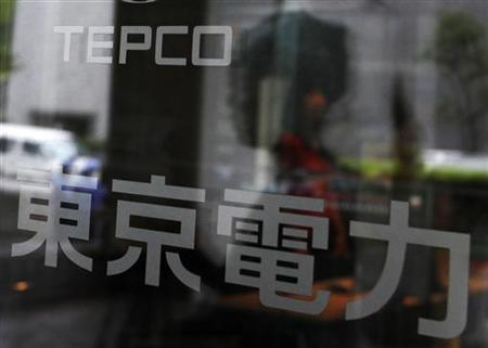 A woman walking into Tokyo Electric Power Co (TEPCO) headquarters building is reflected in the entrance door in Tokyo June 14, 2011. REUTERS/Yuriko Nakao