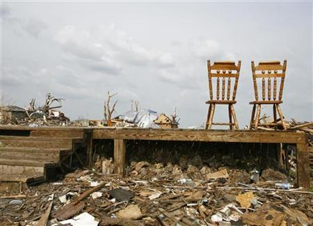 Two kitchen chairs are all that is left in a destroyed house as its foundation is prepared to be bulldozed following the May 22 tornado in Joplin on June 1, 2011. REUTERS/Sarah Conard