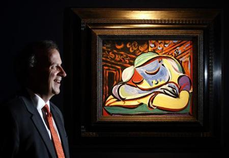 Vice Chancellor of the University of Sydney, Michael Spence, poses with Pablo Picasso's ''Jeune fille endormie'' at Christie's auction house in London June 17, 2011. REUTERS/Luke MacGregor