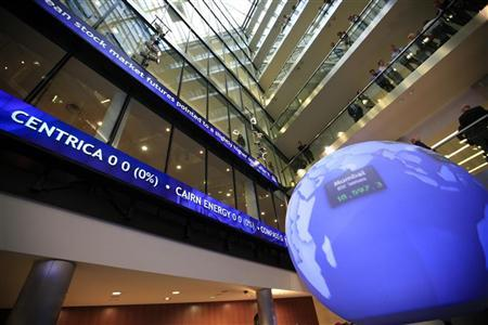 Workers look into the atrium as financial data and news headlines stream accross ticker screens at the London Stock Exchange after Chancellor of the Exchequer George Osborne inaugurated the ceremonial market opening in the City of London, May 10, 2011. REUTERS/Andrew Winning