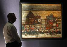 "<p>A Sotheby's employee poses with artist Egon Schiele artwork ""Hauser mit bunter wasche (vorstadt II) / Houses with laundry (suburb II)"" at Sotheby's Auction House in London June 17, 2011. REUTERS/Luke MacGregor</p>"