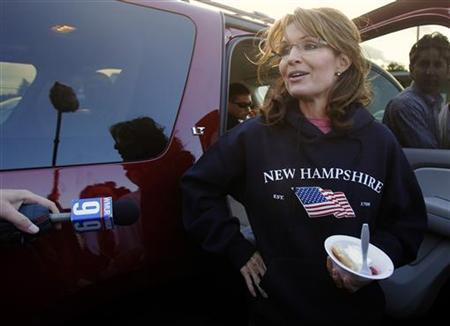 Former Alaska Governor Sarah Palin, wearing a New Hampshire sweatshirt, talks to reporters following a stop at a clam bake at a private residence in Seabrook, New Hampshire June 2, 2011. REUTERS/Brian Snyder