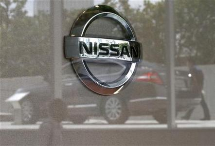 Nissan Motor Co's logo is seen as a car and visitors are reflected on a window at the company showroom in Yokohama, south of Tokyo June 23, 2011. REUTERS/Toru Hanai