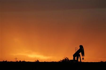 An oil rig is silhouetted against the sunset in St. Lawrence, Texas May 9, 2008. REUTERS/Jessica Rinaldi