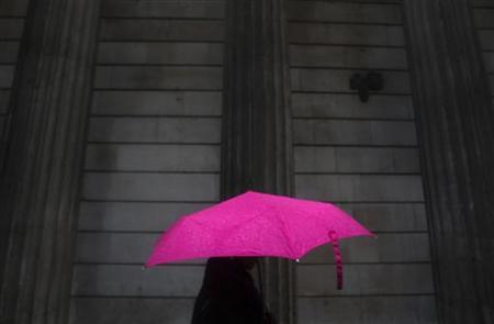 A woman carries an umbrella during a rain shower as she walks past the Bank of England in London November 30, 2009. REUTERS/Andrew Winning