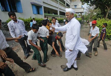 Students touch the feet of veteran  social activist Anna Hazare as a sign of respect as he visits one of his schools in the Ralegan Siddhi village, located in the Ahmednagar district about 250km (155 miles) south east of Mumbai June 17, 2011. REUTERS/Danish Siddiqui