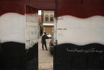 A school door is painted with the colours of Yemen's national flag, as a soldier stands guard, on the first day of the General Secondary Examinations in Sanaa June 26, 2011. REUTERS/Suhaib Salem
